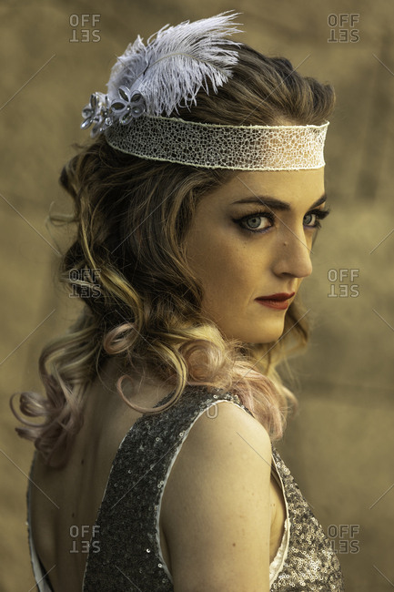 Woman dressed in flashy 1920's dress and headband