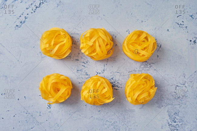 Gluten free corn linguine pasta coils on blue background. Fodmap compliant.