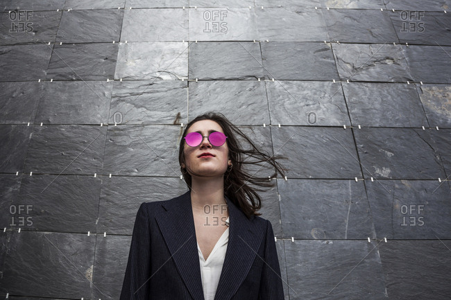 young, serious and brunette girl with jacket and sunglasses in front of blackboard slate wall