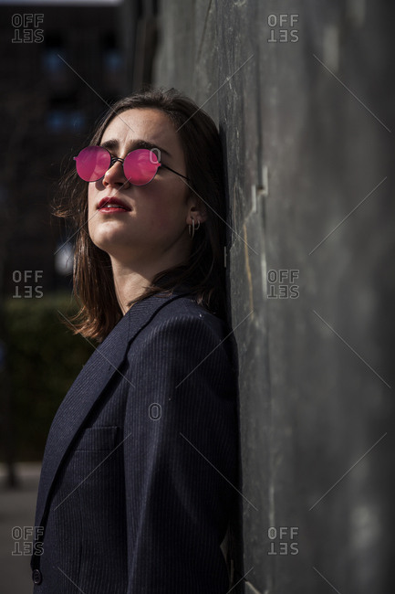 young, serious and brunette girl with jacket and sunglasses in front of wall of slate plates and look to the right