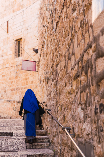 Back view of unrecognizable female in traditional clothes walking up shabby stairs near rough wall of ancient building on street of Jerusalem, Israel