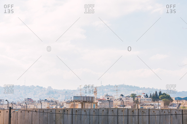 Drone view of old city of Bethlehem behind concrete boundary wall on sunny day