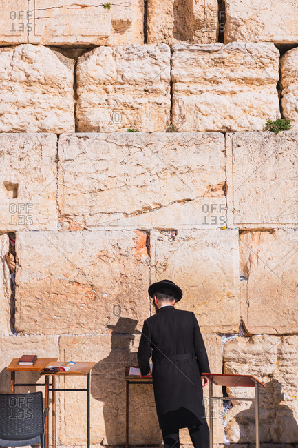 Back view of orthodox Jewish man standing near old stone wall on sunny day in city of Jerusalem in Israel