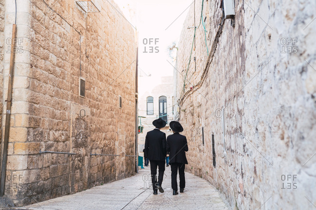 Back view of two orthodox Jewish men walking together on narrow old street of Jerusalem, Israel
