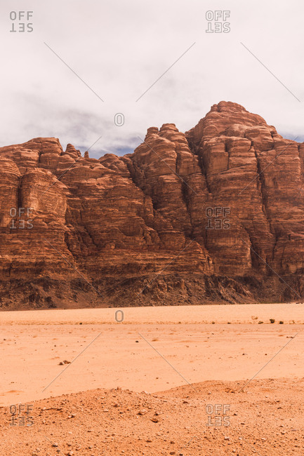 Landscape of majestic solid cliffs of sandstone rock in empty desert valley of Wadi Rum, Jordan