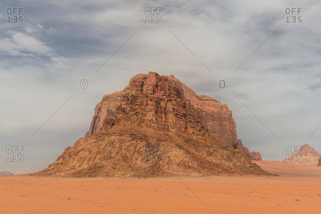Monumental rocky cliff of sandstone in empty Wadi Rum desert valley, Jordan