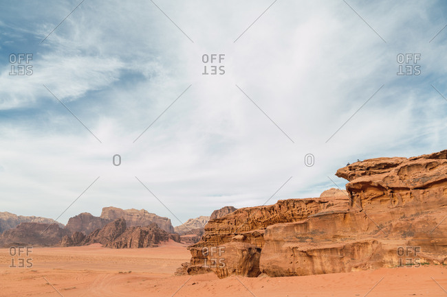 Desert landscape of majestic canyon of orange sandstone cliffs under blue sky, Jordan
