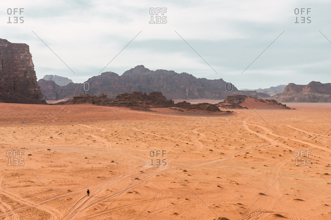 Panoramic view of desert valley of Wadi Rum with single wanderer on sandy terrain against cliffs, Jordan