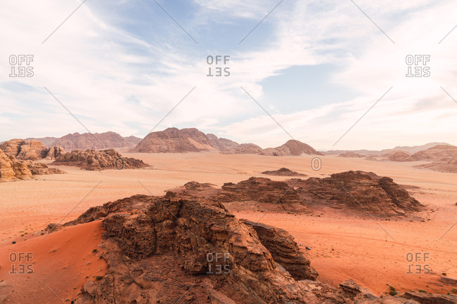 Landscape with desert rocky cliffs of red color in empty terrain under blue sky, Jordan