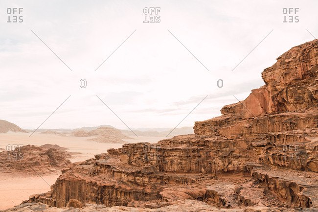 Rough sandstone cliffs of canyon in picturesque valley of Wadi Rum in light haze, Jordan