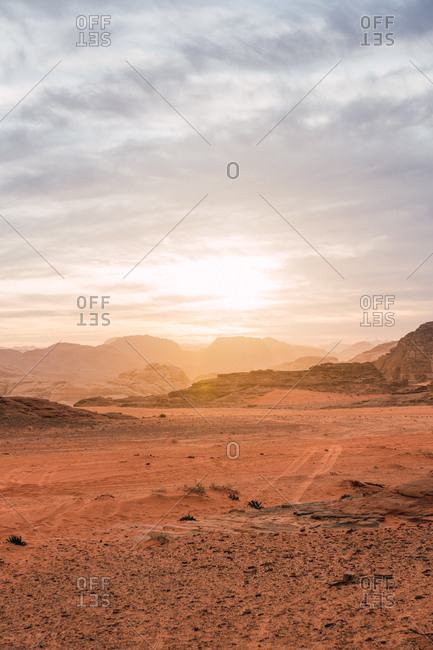 Landscape of red dry valley of Wadi Rum with cliffs in bright sunlight, Jordan