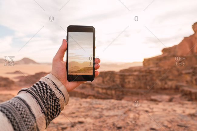 Crop male hand in sweater holding smartphone taking photo of picturesque desert of Wadi Rum desert in Jordan