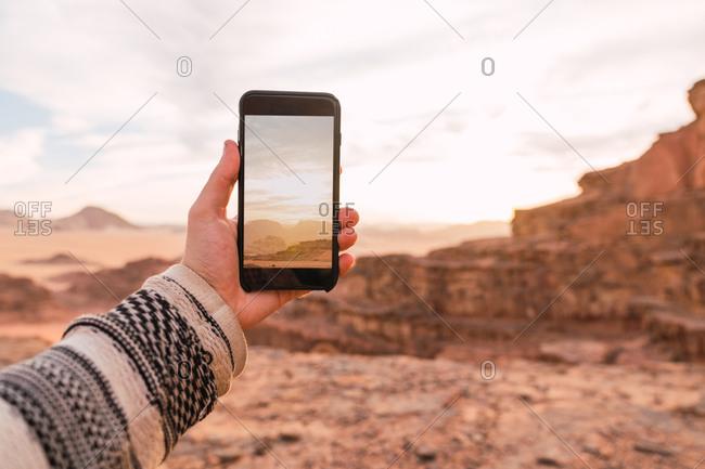 Crop male hand in sweater holding smartphone taking photo of picturesque desert of Wadi Rum desert in Jordan