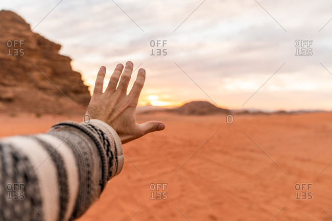 Crop male hand outstretched toward sunset sky in red desert valley of Wadi Rum, Jordan