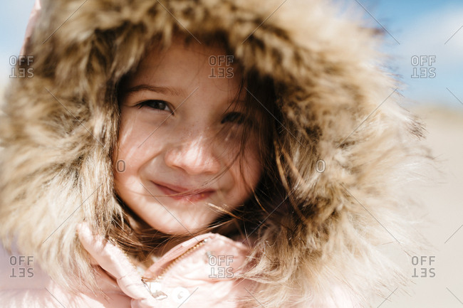 Little girl smiling with her hood on