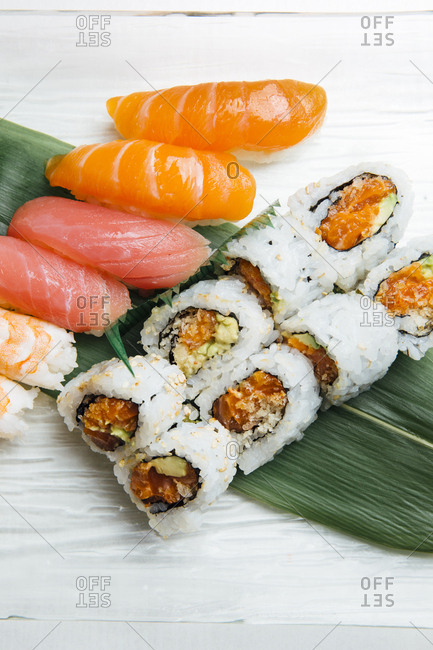 Sushi and salmon rolls served on banana leaf