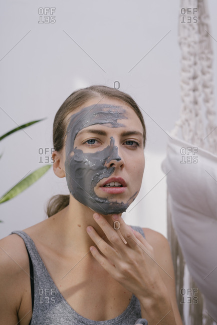 Young beautiful woman at home put on a beauty face mask