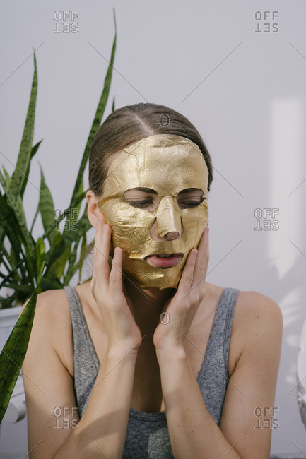 Young beautiful woman at home put on a golden face mask
