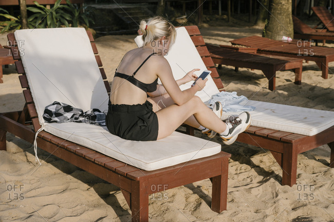 Young blonde sits back on the beach on a sun lounger