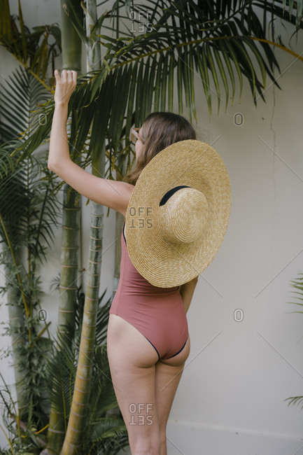 Beautiful young woman in a swimsuit is standing backwards in a hat