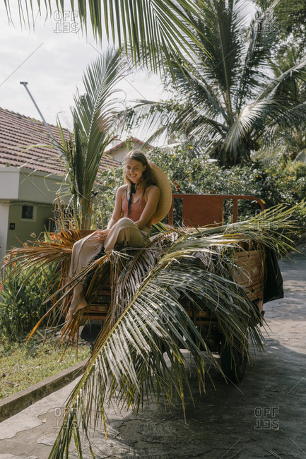 Beautiful young woman sitting on a gardener's scooter with palm leaves