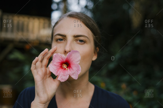 Close portrait of a young beautiful woman with a flower in her mouth