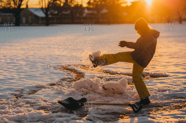 Boy kicks a ball of snow
