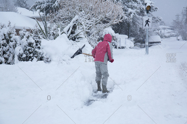 Canada Victoria, woman shoveling snow from sidewalk.