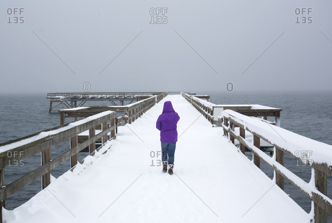 Canada Victoria,  woman walking in Sidney pier in snow storm.