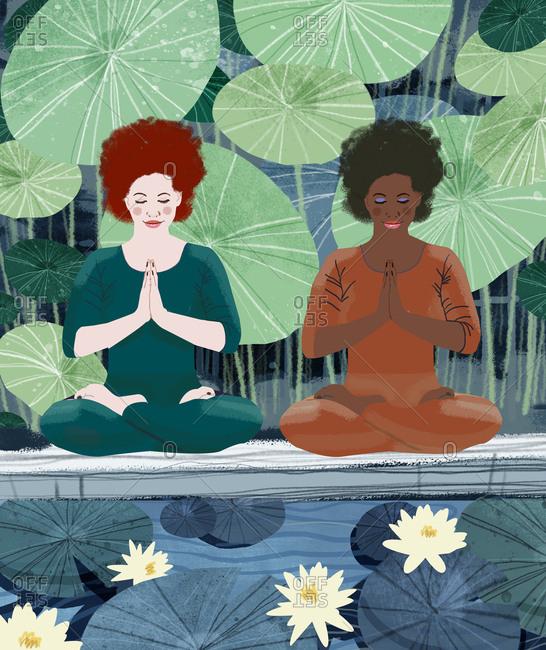 Two women in lotus yoga pose