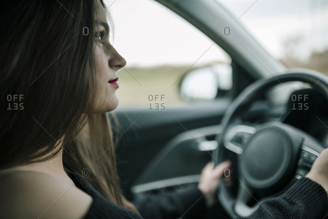 Young woman is in a car with her hands on the steering wheel