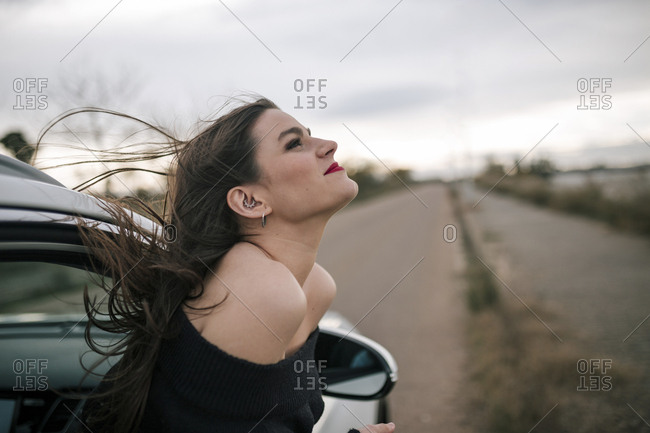 Young woman goes out the window of a car to enjoy the outdoors