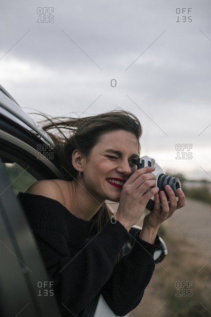 Young woman goes out the window of a car and takes pictures with a camera