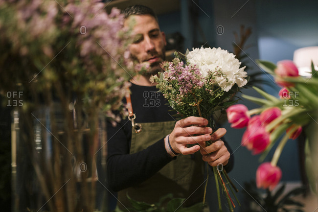Man with apron making a bunch of flowers at a florist shop