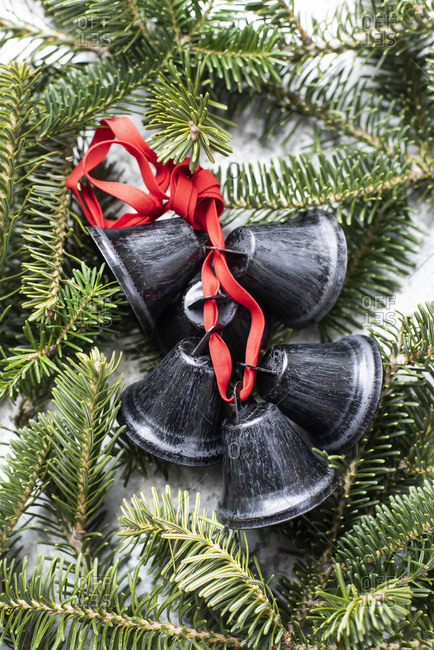 Black metal bells tied with red ribbon on twig of Christmas tree