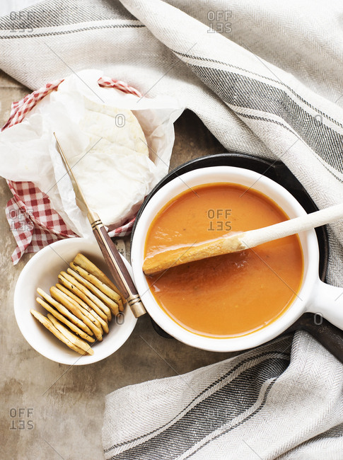 A bowl of sweet potato carrot soup with brie cheese and crackers