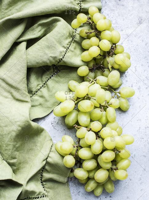 Green grapes close to a green linen cloth