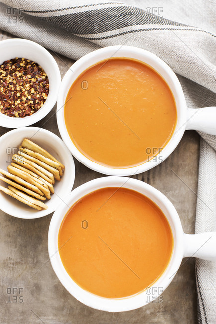 Two bowls of sweet potato carrot soup with crackers