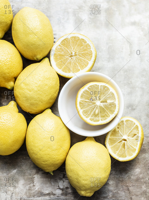 Whole lemons and cut in half on a light background