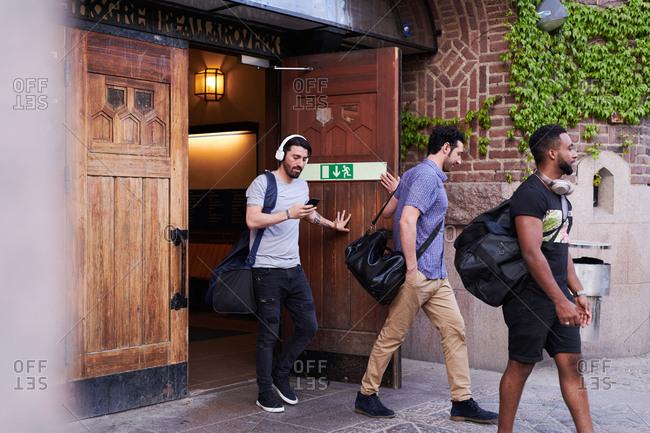 Multi-ethnic male students leaving language school