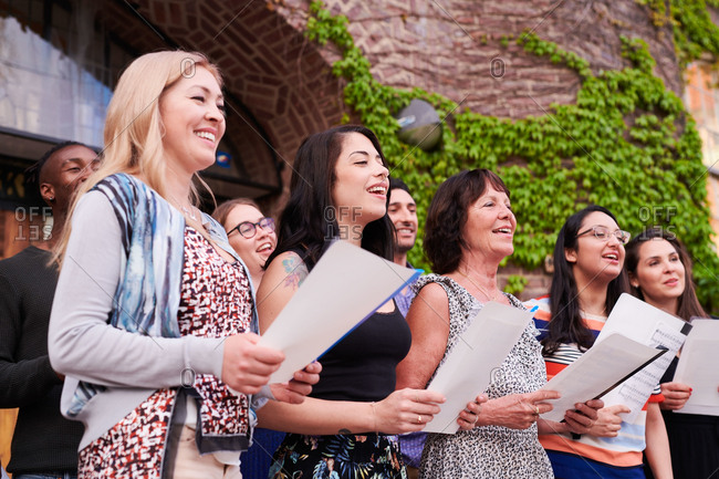 Multi-ethnic students singing in choir together outside language school