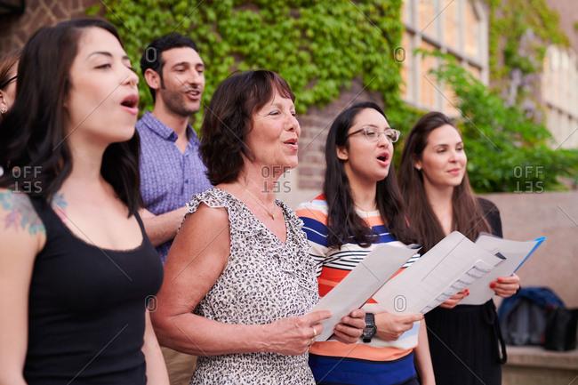 Multi-ethnic choir singers performing outside language school