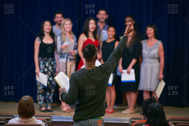 Male conductor with arm raised directing choir in auditorium