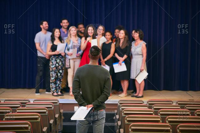 Musical teacher listening to choir on stage in auditorium of language school