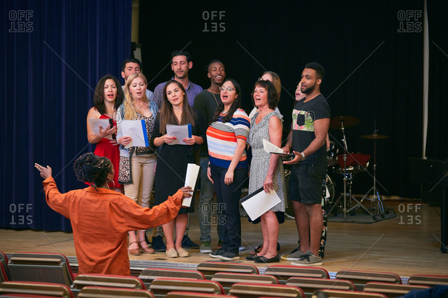 Teacher directing choir on stage in language school
