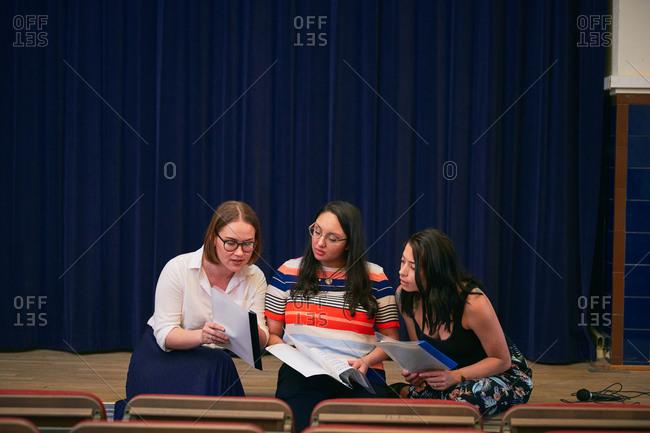 Multi-ethnic women discussing over musical sheets in auditorium