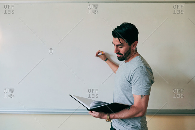 Confident male teacher holding book while writing on whiteboard