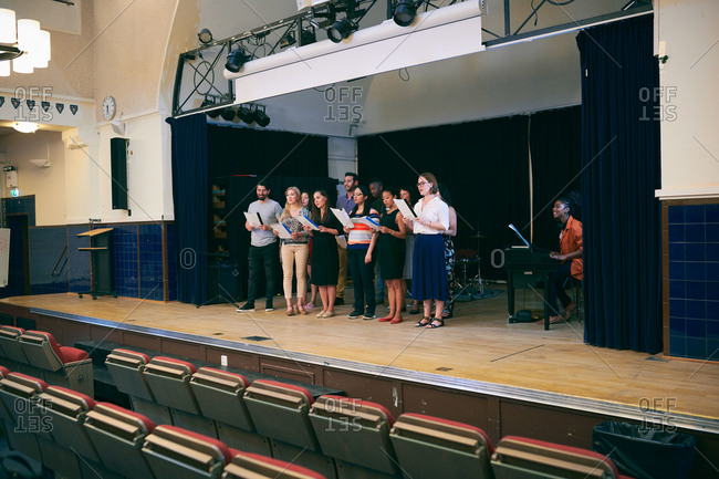 Friends with music sheets singing at choir practice