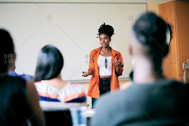 Confident young woman gesturing while teaching students in class