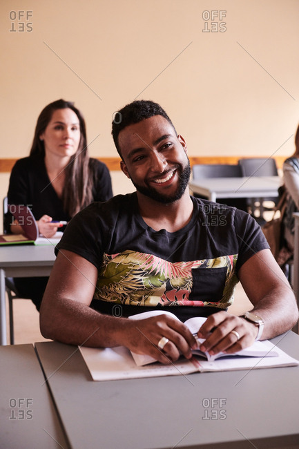 Confident student smiling while sitting at desk in language school